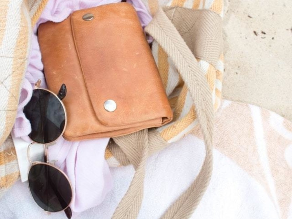 purse with sunglasses and a towel