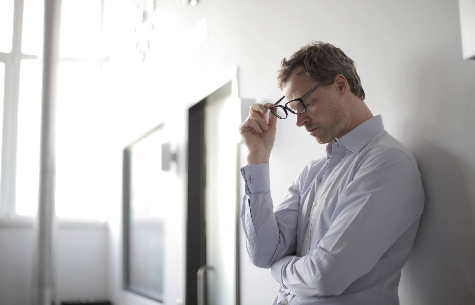 guy with glasses leaning up against a wall in frustration