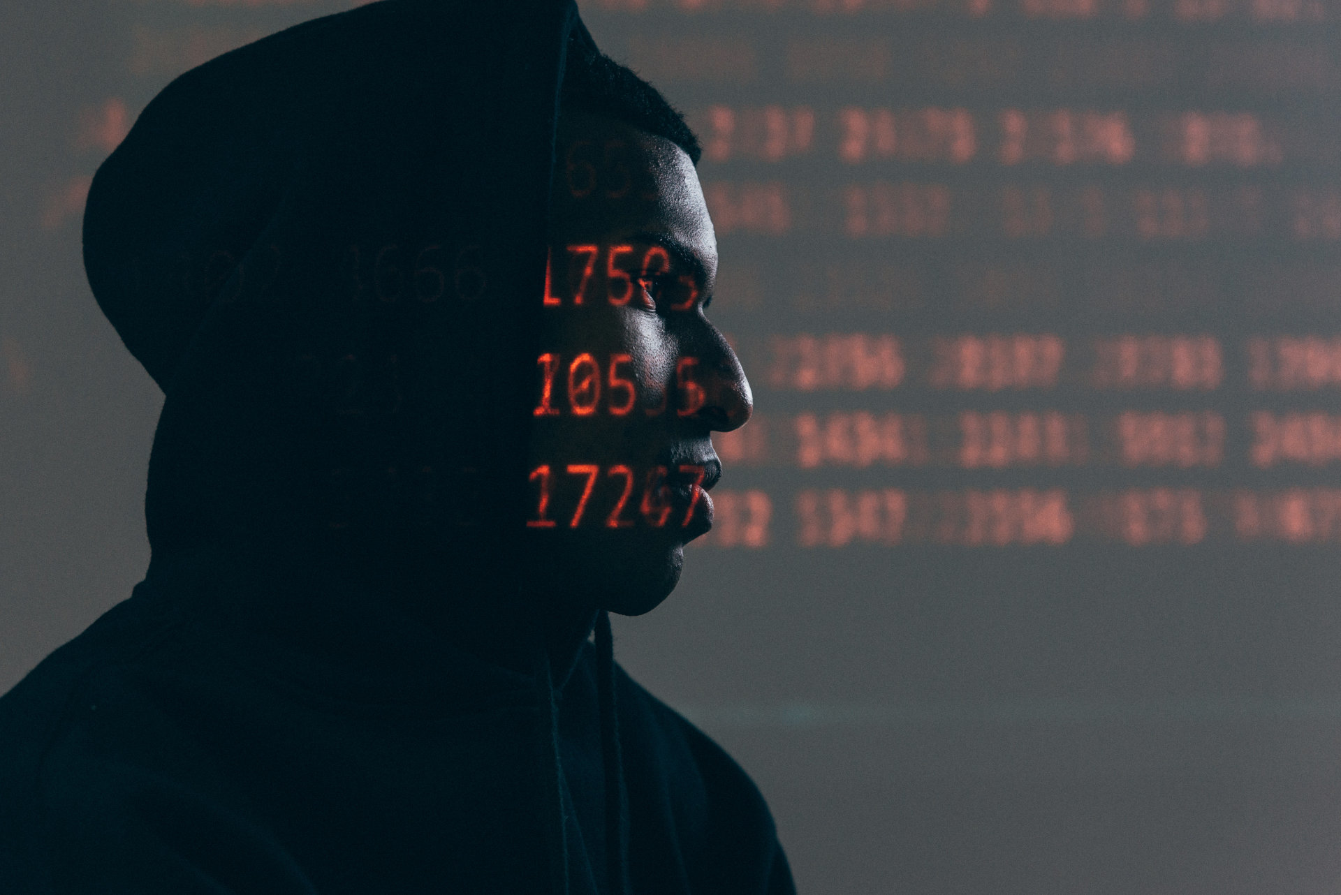 guy in black hoodie with code in background